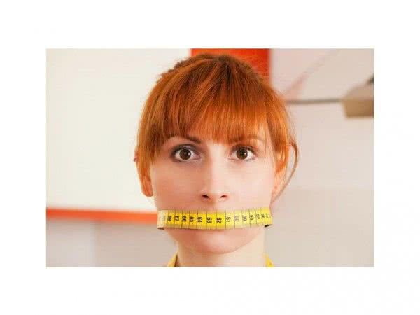 woman with measuring tape over her mouth